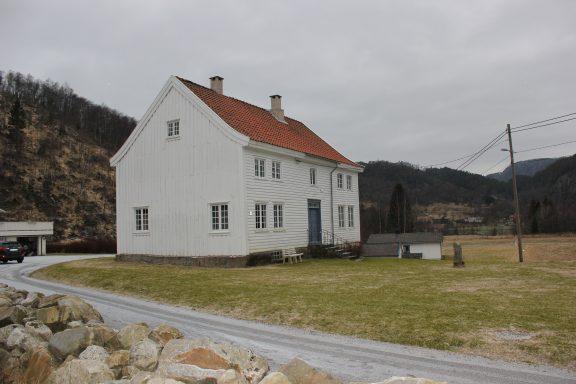 Bilde av gården fra siden. Her sees tydelig den svaie gesimsen på saltaket til våningshuset.Foto: Marit Vestvik Riksantikvaren