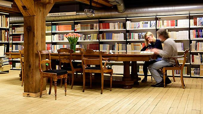Mennesker som sitter og leser rundt et bord i biblioteket.