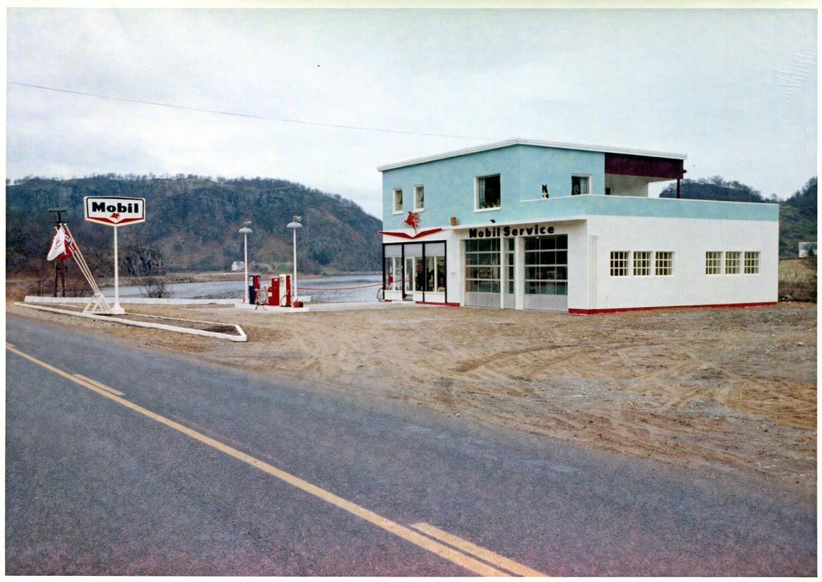 Høsten 1960 ble bilsalget fritt i Norge. Det betydde at en kunne kjøpe bil uten tillatelse fra myndighetene. Etter hvert innebar dette også flere biler på norske veier og bedre tilbud på bensinstasjonene i takt med økt etterspørsel. På denne bensinstasjonen i Egersund er det tydelig at verkstedet utgjør en sentral del av virksomheten. Kanskje til og med sjefen sjøl bodde i etasjen over?
