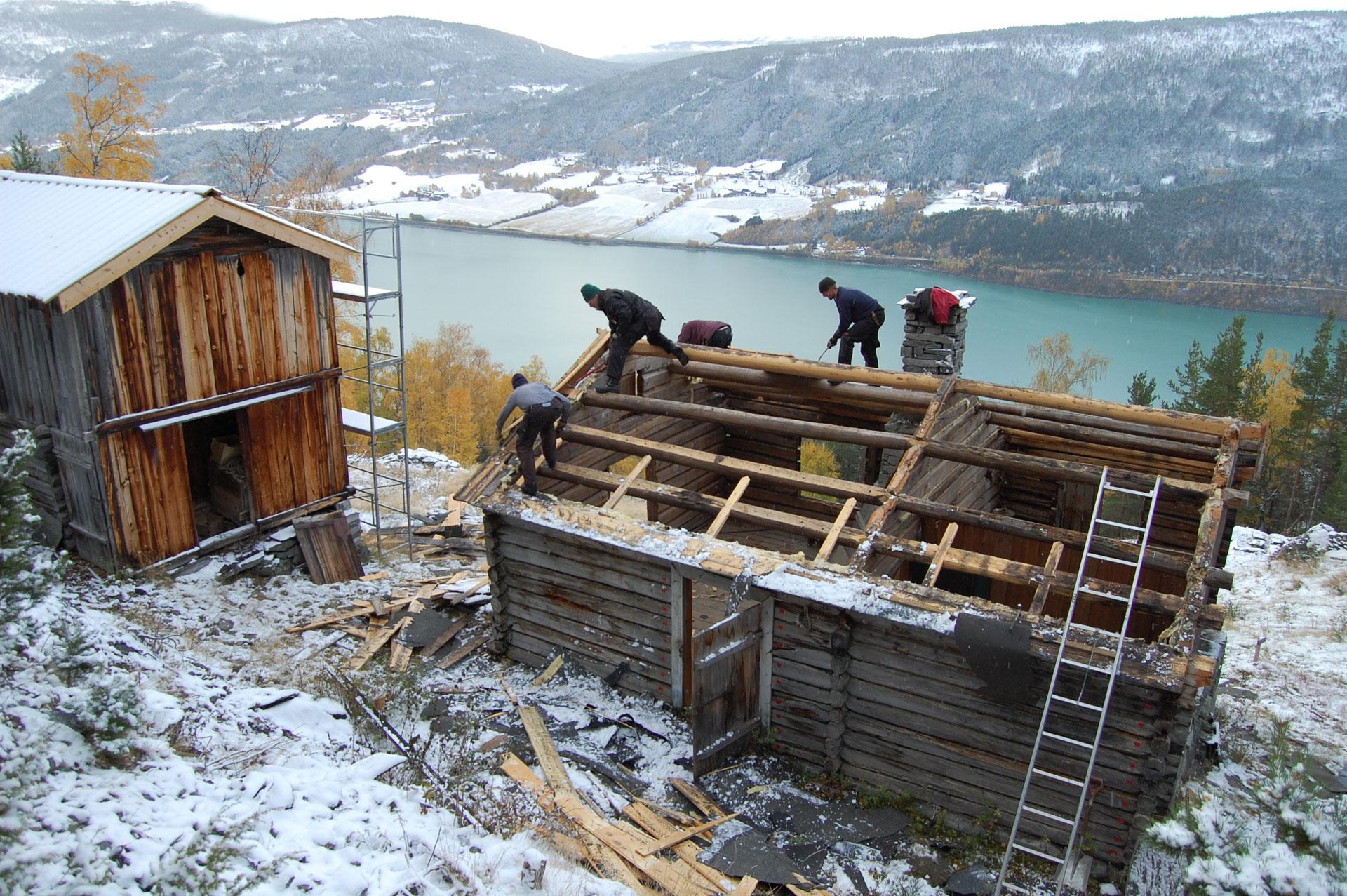 Håndverkere på tak av et hus. Bildet viser et næmingoppdrag ved Hjerleid. Næmingene (elevene) restaurerer et hestgjeterstue i Nordherad i Vågå.