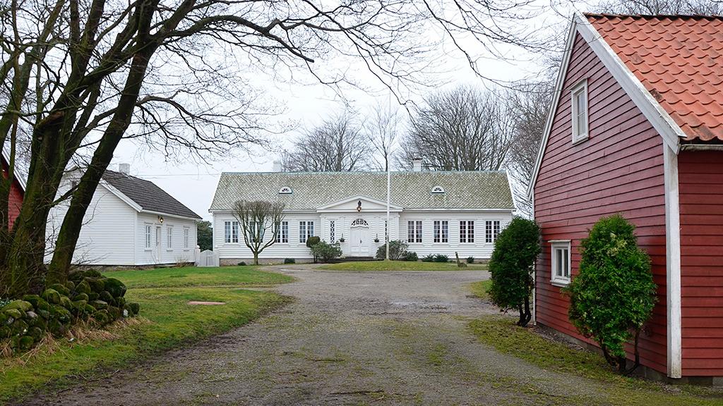 Bilde av Innkjørselen til tunet på Huseby kongsgård som viser tunstrukturen fra middelalderen med forpakterbolig, hovedbygning og den i flere omganger påbygde låven. Foto: Vest-Agder fylkeskommune.