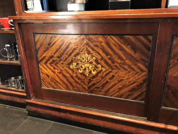 Bildet viser en detalj av interiøret av mahogni med intarsia (innskoren dekor) i messing Foto er tatt av Linn Brox Riksantikvaren