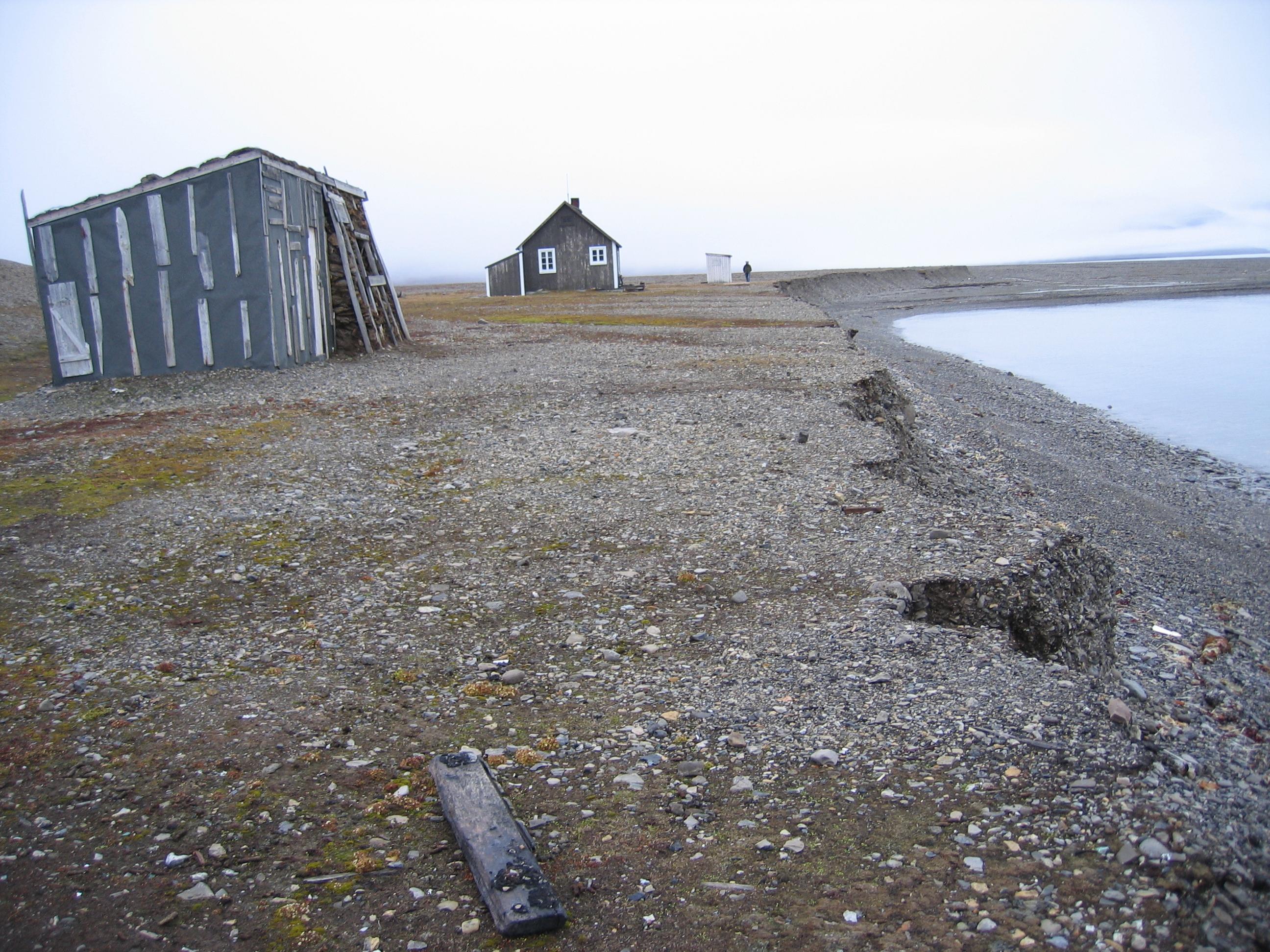 Denne fangststasjonen på Svalbard står i fare for å bli tatt av bølgeerosjon. Den eldste hytta (t.v.) er allerede flyttet innover en gang og nå skal hele stasjonen flyttes til et tryggere område. Foto: Susan Barr / Riksantikvaren