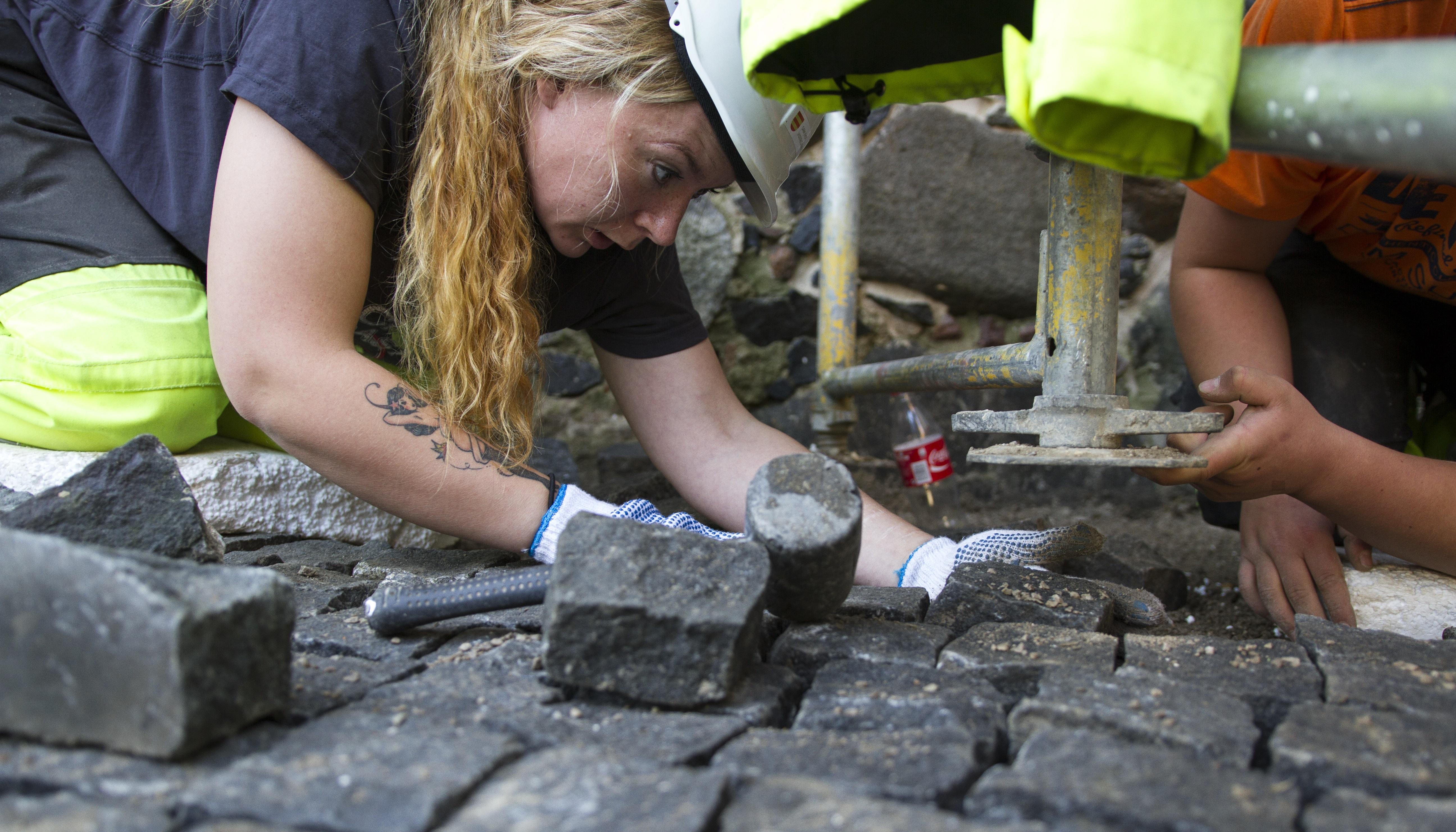 Elev ved anleggslinjen Liv Anita Tønnesen legger stein utenfor synagogen. Foto: Håkon Halgrimsen Riksantikvaren