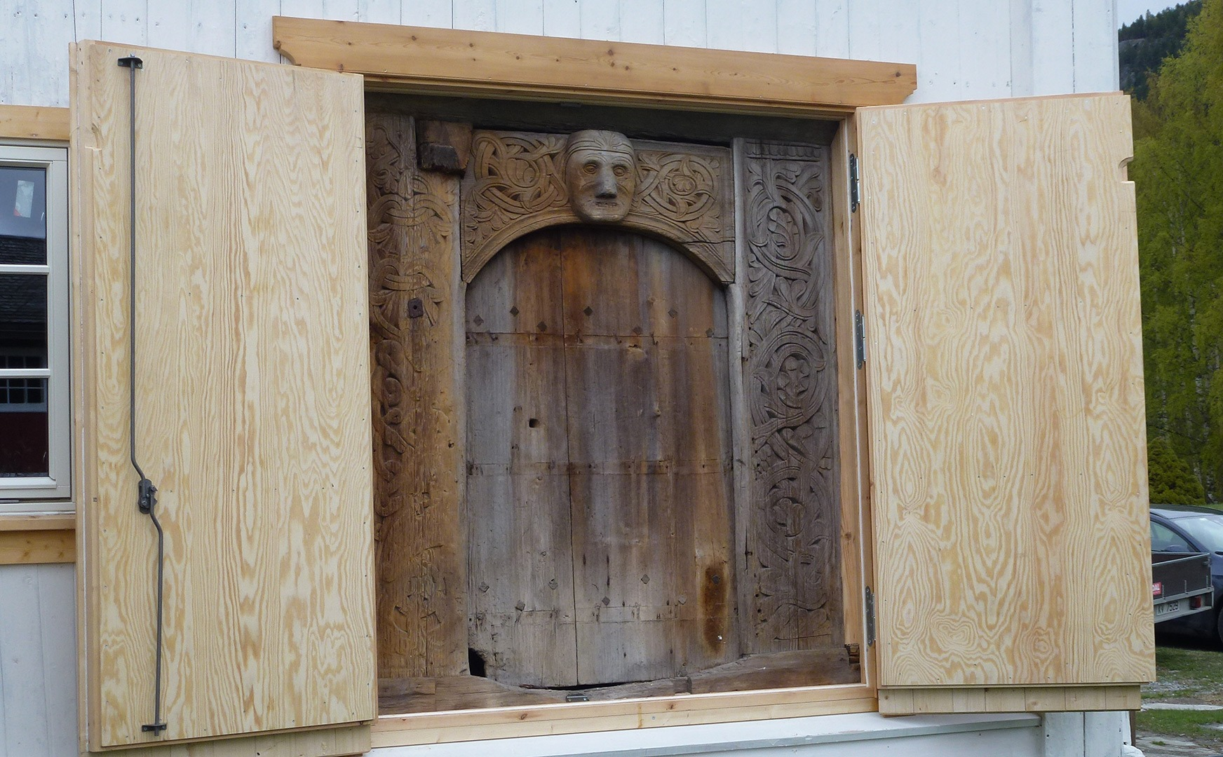 Bak kledningen på sørveggen skjuler denne portalen seg – en rundbuet praktportal som er typisk for romansk stil. I dag er portalen beskyttet av en dørlem men ettersom portalen er så godt bevart har den trolig også vært beskyttet for vær og vind tidligere. Foto: Kjell Andresen Riksantikvaren
