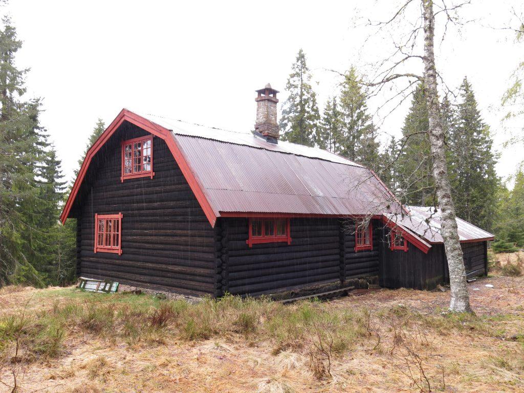 Bilde av hytta på Rudsæter. Det er en toetasjes laftet tømmerbygning med smårutede vinduer, mansardtak i blikk og åpen sval. Foto: Ingeborg Magerøy, Riksantikvaren