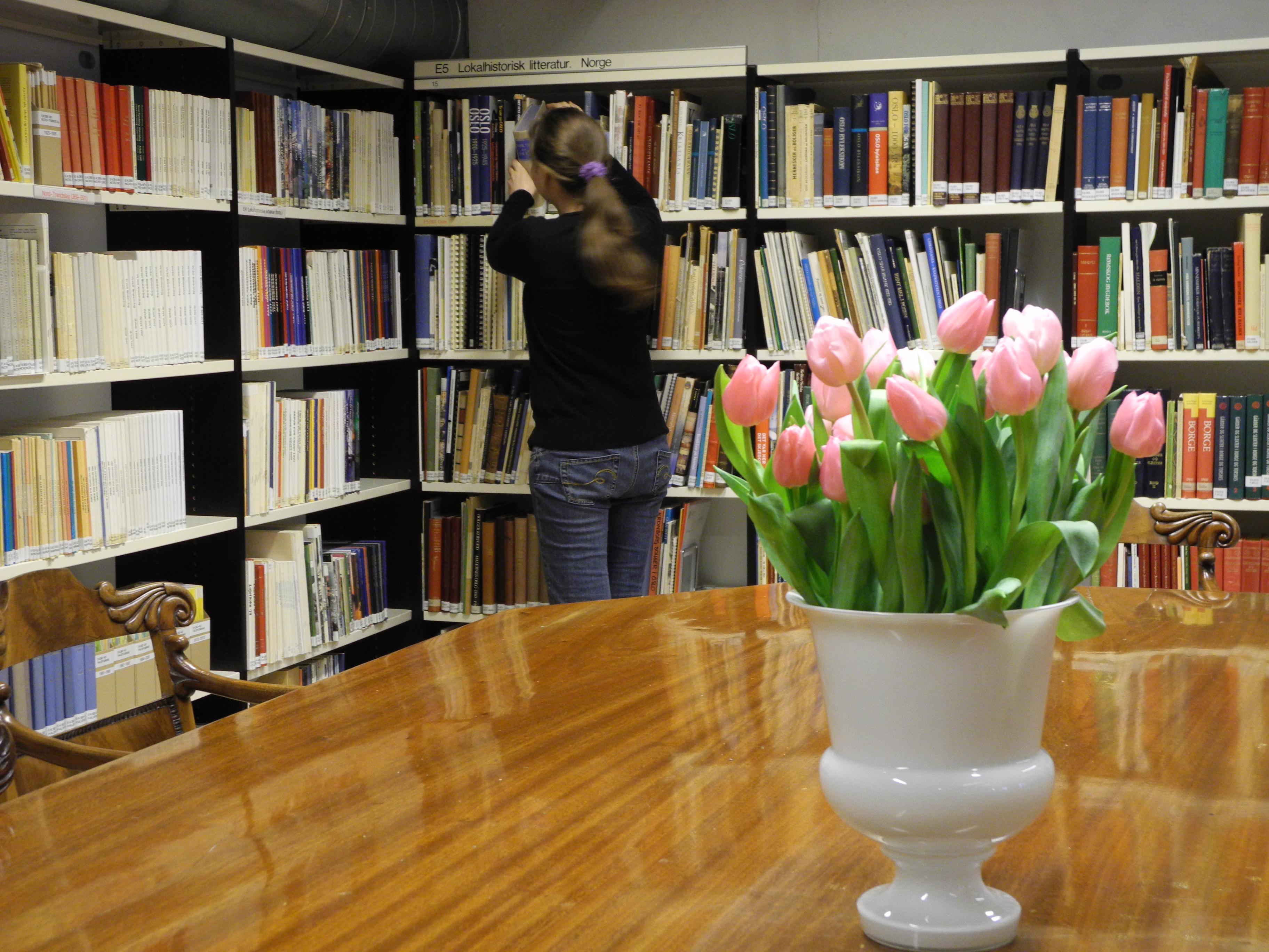 Bibliotekbruker henter ei bok fra hyllene
