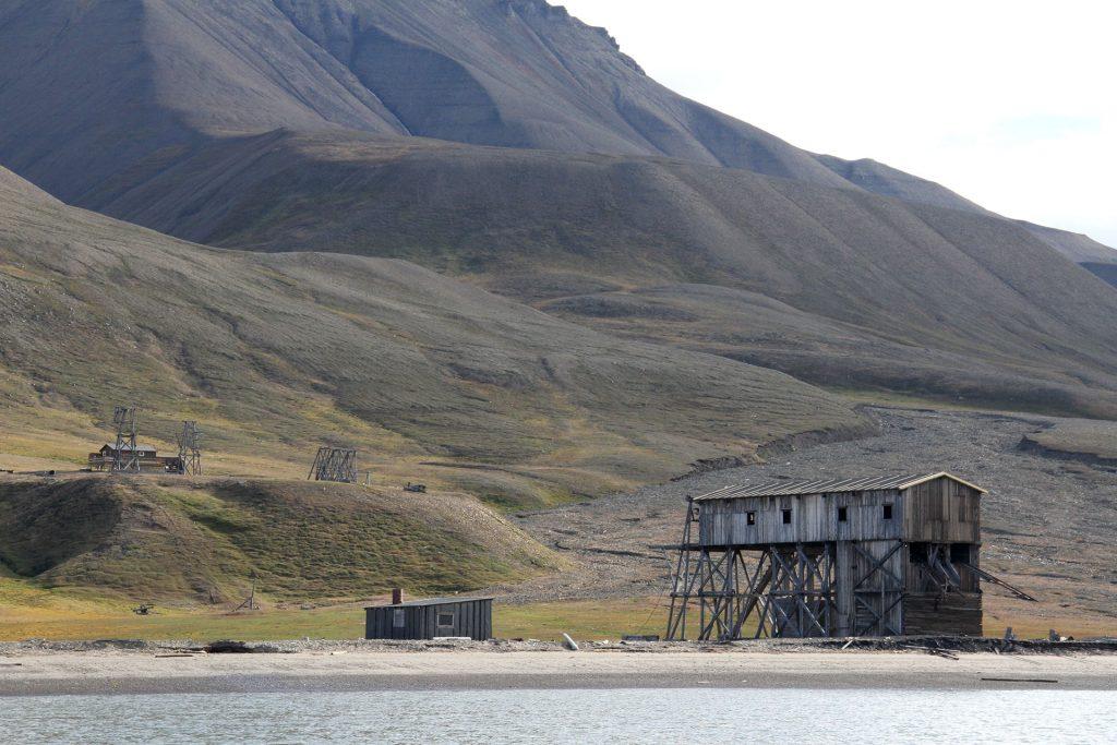 Havet gnager seg stadig nærmere den fredete taubanestasjonen i Hiorthamn på Svalbard. Foto: Siri Wolland Riksantikvaren