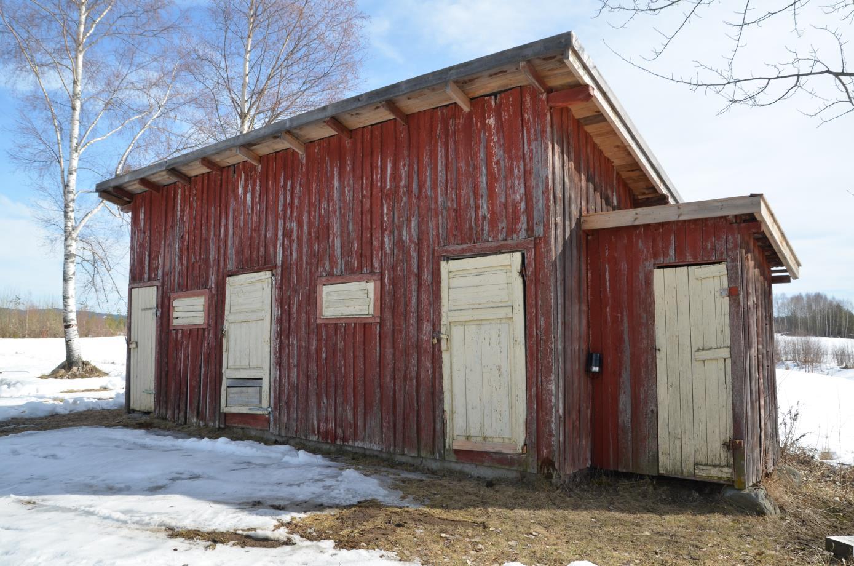 Uthuset / stallen er oppført i bindingsverk med rødmalt tømmermannspanel (over- og underliggere). Bygningen står på enkel oppmuring av naturstein. Foto: Riksantikvaren 2019