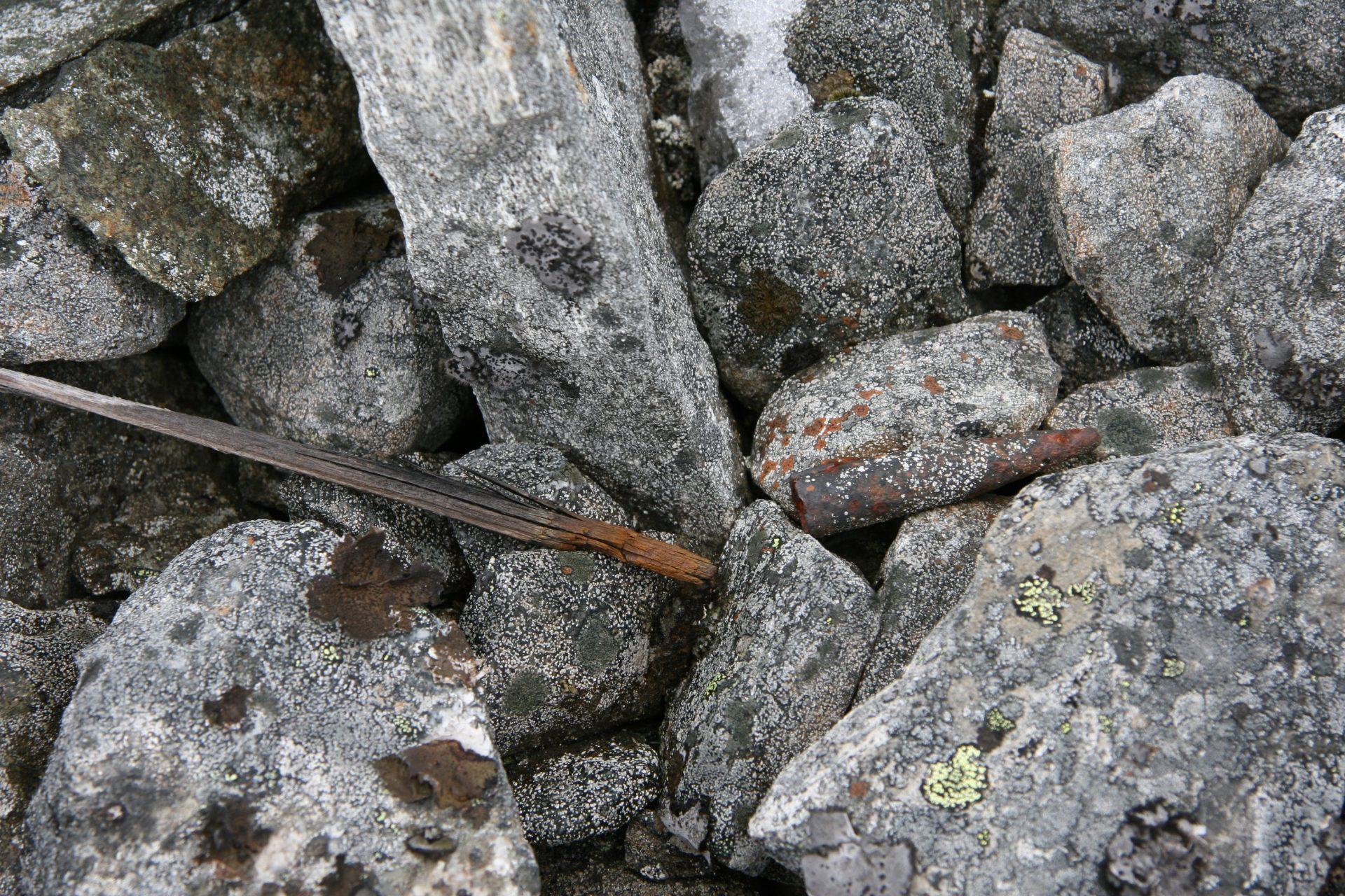 Bildet viser antakelig en skremmepinne i tre som er brukt i forbindelse med reinsjakt. Den har nylig smeltet fram etter å ha ligget under snø og is i mange hundre år. Gjuvfonni ved Juvasshytta. Foto: Terje Hovland / Riksantikvaren