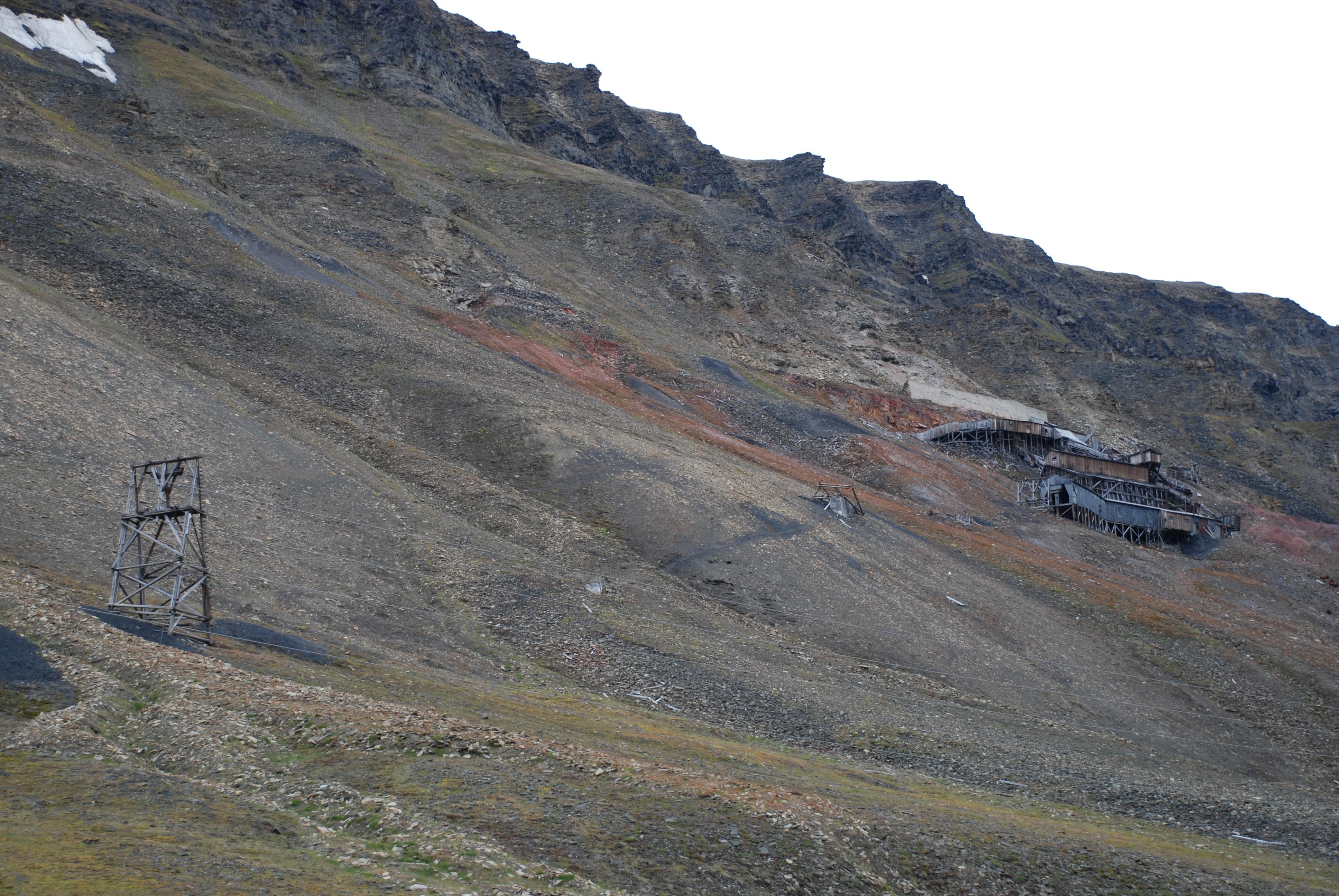 De ikoniske rekkene med taubanebukker på Longyearbyens fjellsider er svært utsatt for utglidning i bakken ettersom permafrosten tiner samt for stein- og snøras. I denne rekken til Gruve 2 er to av bukkene tatt av et snøras fra fjelltoppen. Foto: Susan Barr / Riksantikvaren