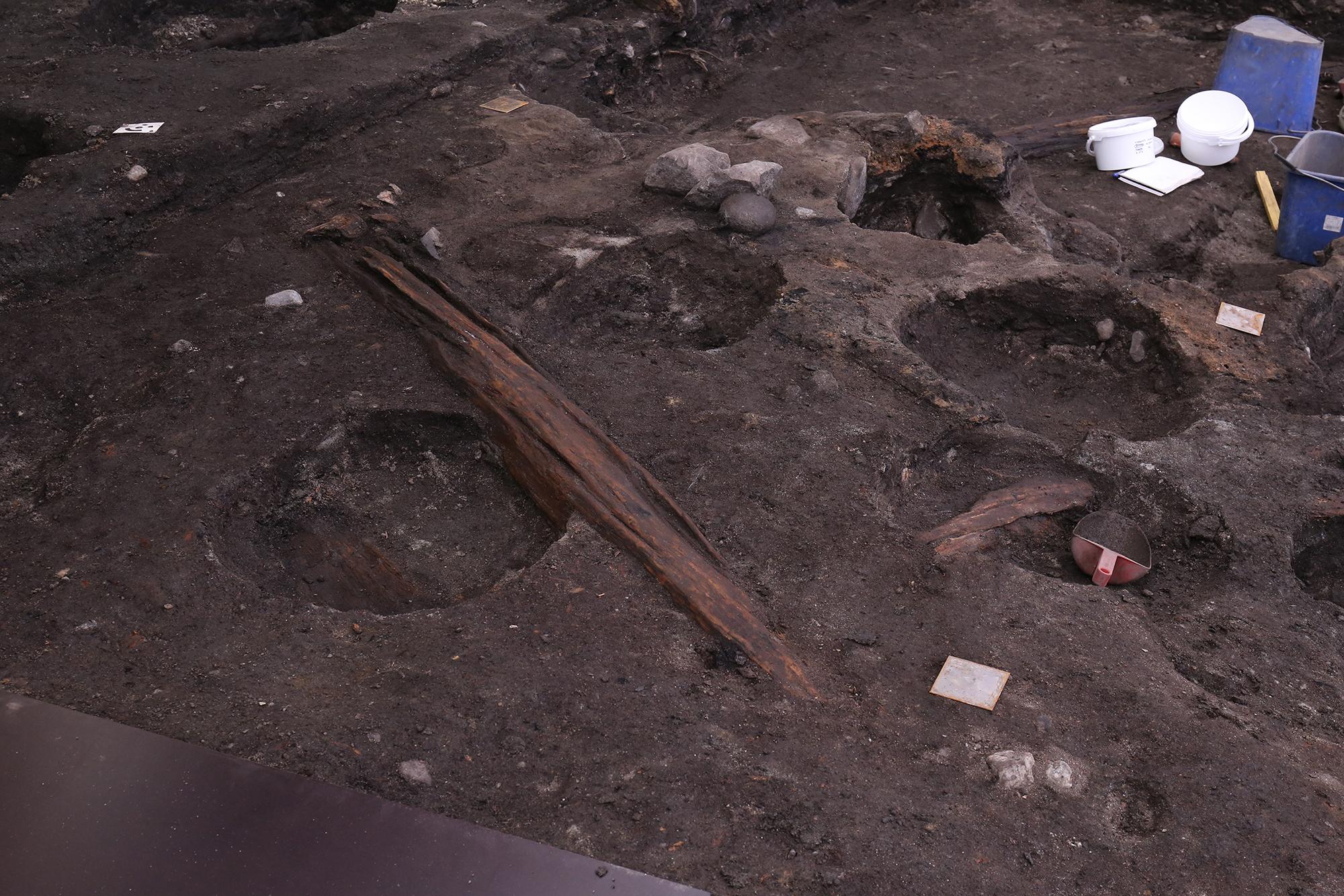 Bilde av Deler av trebygning som arkeologene begynner å få fram i felt. Foto: Anna K. Wändahl, NIKU