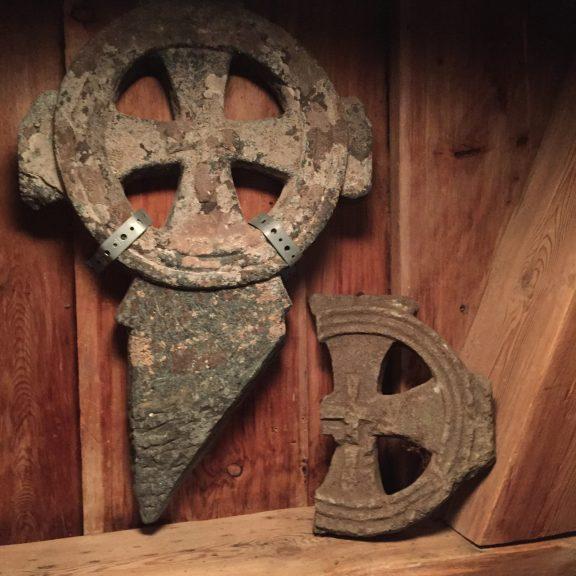 Bilde av 2 hjulkors. Hjulkorset er så godt som identisk med hjulkorset som ble funnet i et gravkammer under kirkegulvet ved restaureringsarbeider på 1930-tallet. Likheten mellom hjulkorsene tilsier at de kan være fra samme gravmonument. Foto: Åse Bergan