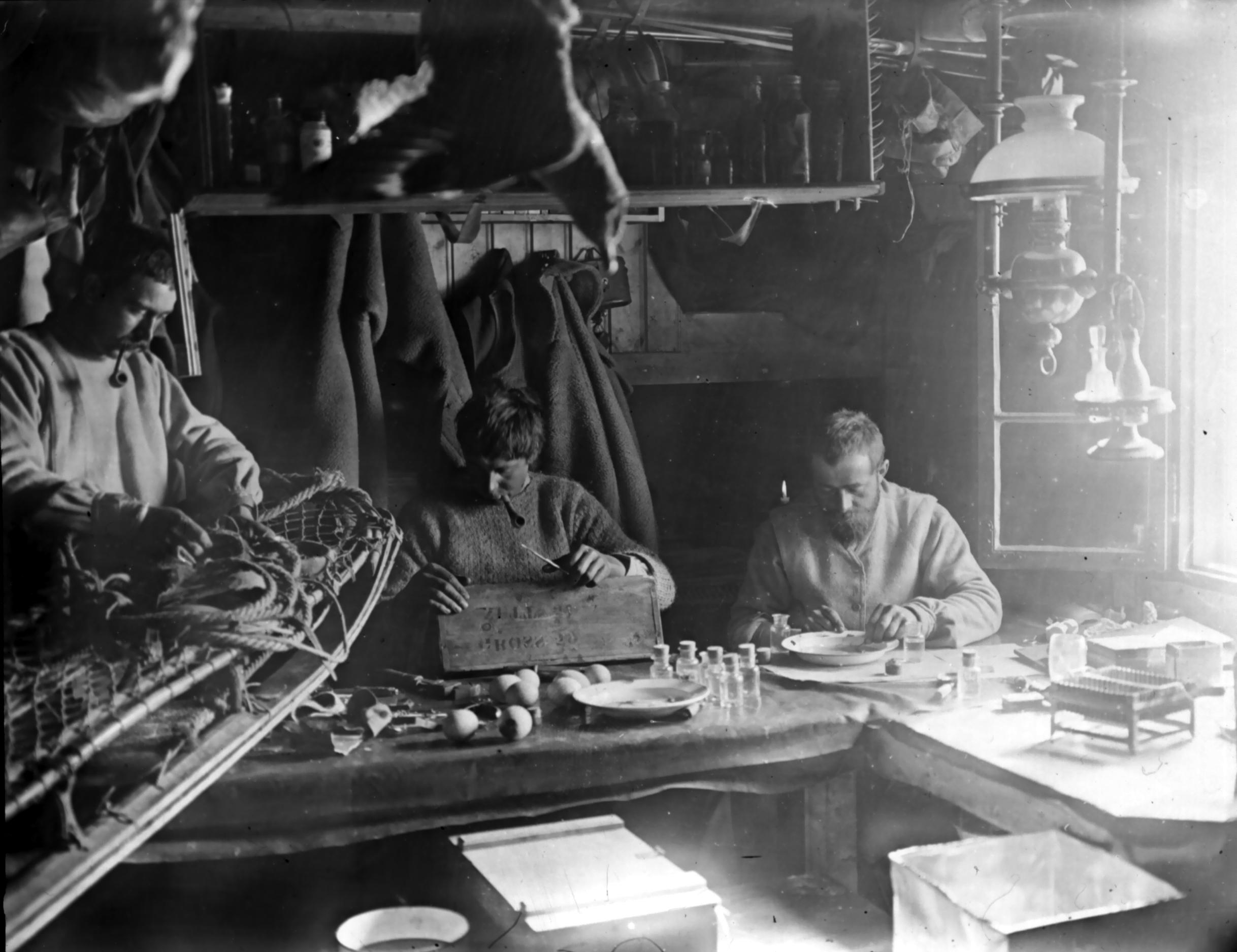 Bildet viser Borchgrevink og to av hans menn i bolighytten. Fotograf er Carsten Borchrevink, og bildet lånt fra Norsk Polarinstitutt.