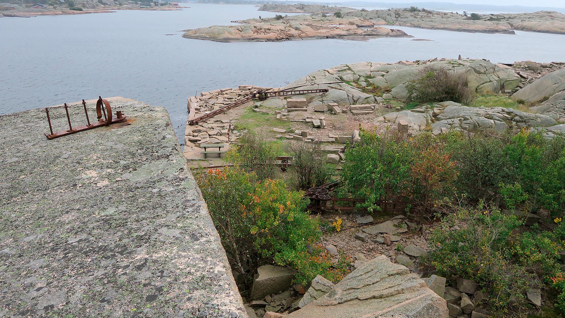 Foto av Utsikt over en del av området med granittblokker liggende i terrenget, og med en av kranene liggende på bakken. Fotografert av Ståle Arfeldt Bergås