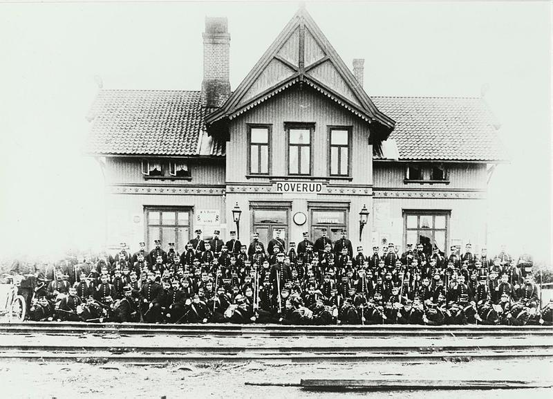 Foto av Roverud Jernbanestasjon med arbeidsstyrken foran. Fotgraf er Olga Kristoffersen, og bildet er hentet fra Riksantikvarens arkiv.