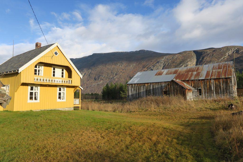 Bilde viser Våningshuset med en av de karakteristiske verandaene, her på gavlveggen. Låven ligger i utkant av tunet. Foto er tatt av Ståle Arfeldt Bergås, Riksantikvaren