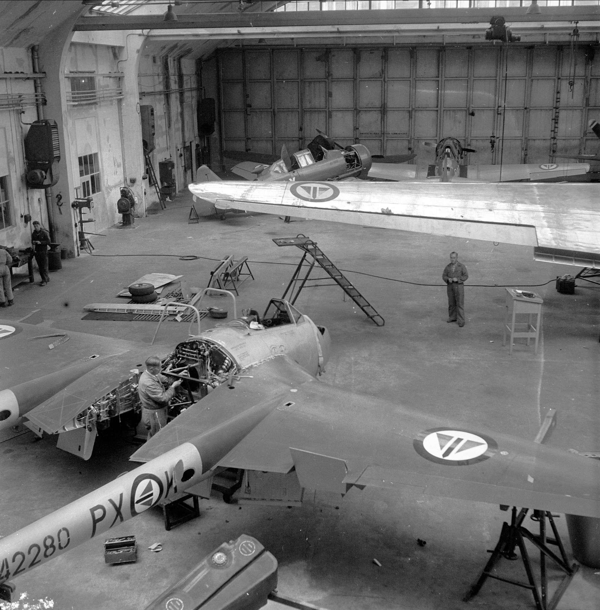 Bildet viser Vedlikehold av fly ved Kjeller, i forkant en DH Vampire, vingen til en DC3 Dakota og to skolefly av type North American T-6/J Harvard. Bildet er tatt i 1952 i forkant av 40-års markeringen til Kjeller. Foto er lånt fra Dagbladet/Norsk Folkemuseum