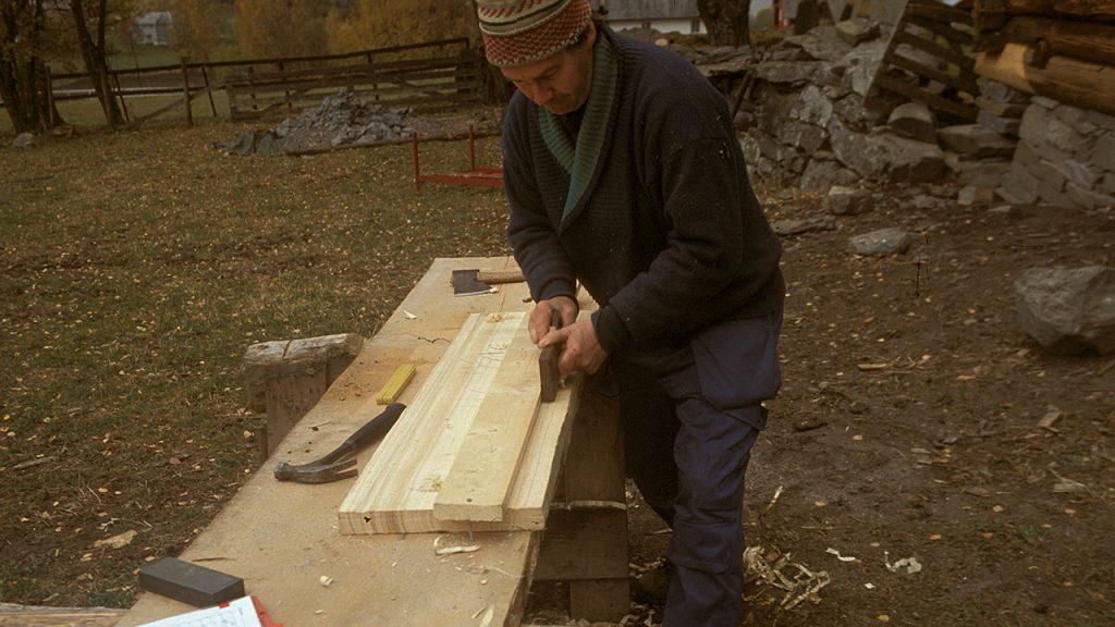 Bildet viser høvling av profil på takbord til støpulen ved Lomen stavkirke. Foto: Hans Marumsrud