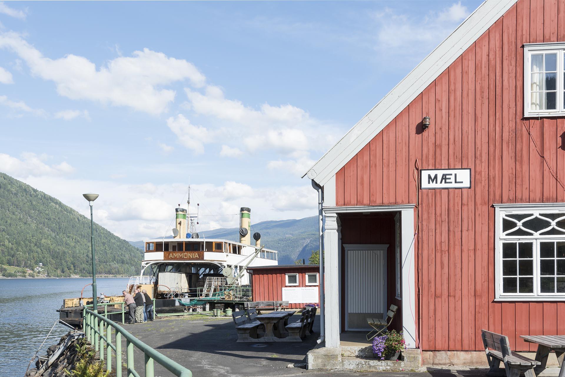Bildet viser Mæl stasjon på Rjukanbanen med Ammonia i bakgrunnen. Foto er tatt av Per Berntsen
