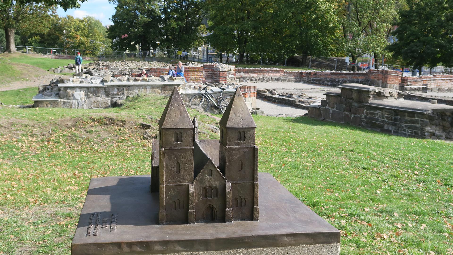 Bilde av bronsemodellen av Mariakirken sett rett forfra. I bakgrunnen er ruinene av kirken. Foto er tatt av Turid Årsheim fra Riksantikvaren