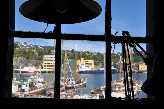Bilde tatt innenifra verkstadbygget. Det er god utsikt til båtmiljøet i vågen utanfor verftet. Foto er tatt av Hege Skalleberg Gjerde, Riksantikvaren