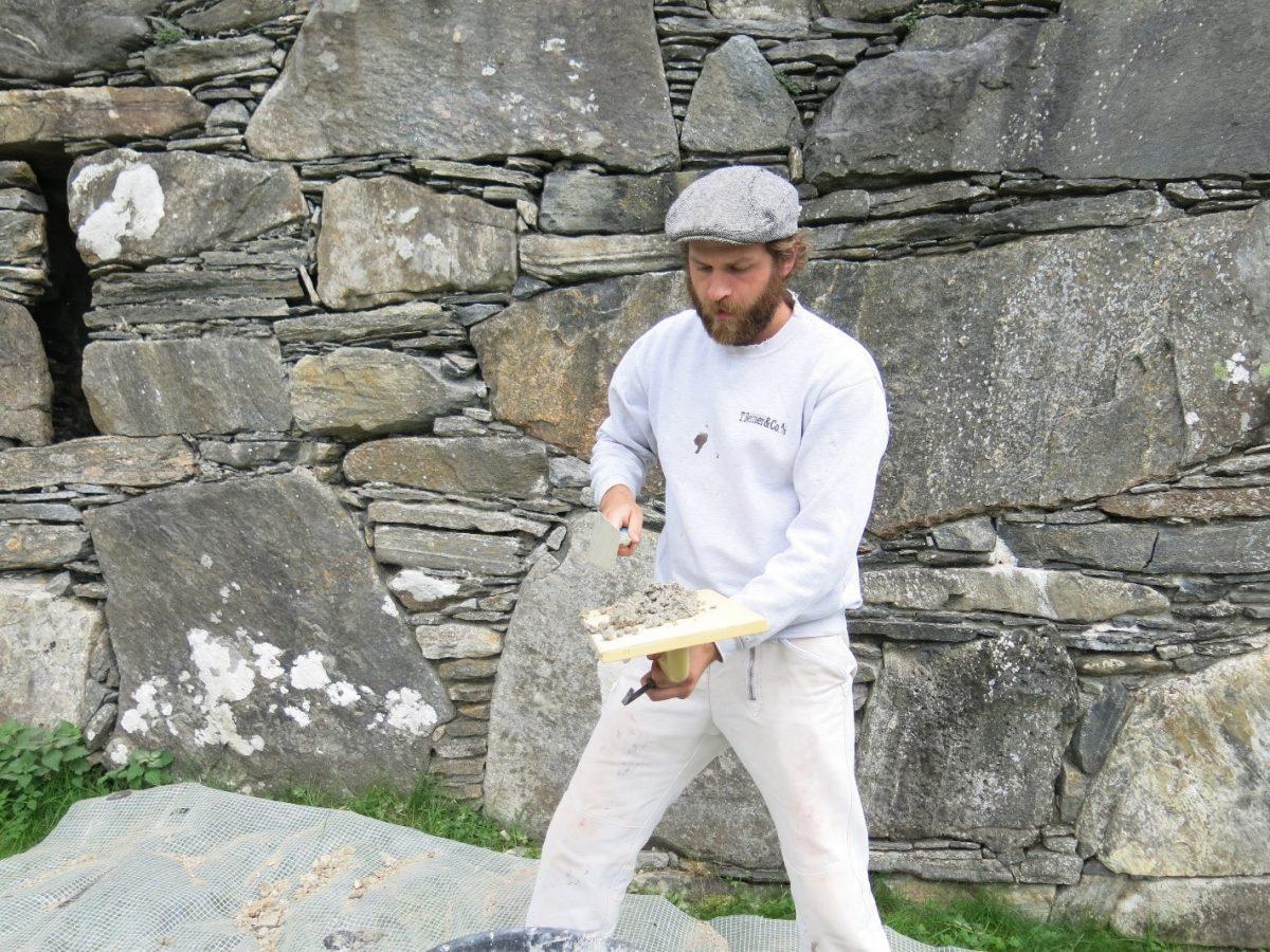 Håndverker jobber foran steinvegg