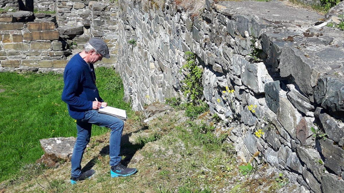 Person noterer detaljer i steinmur