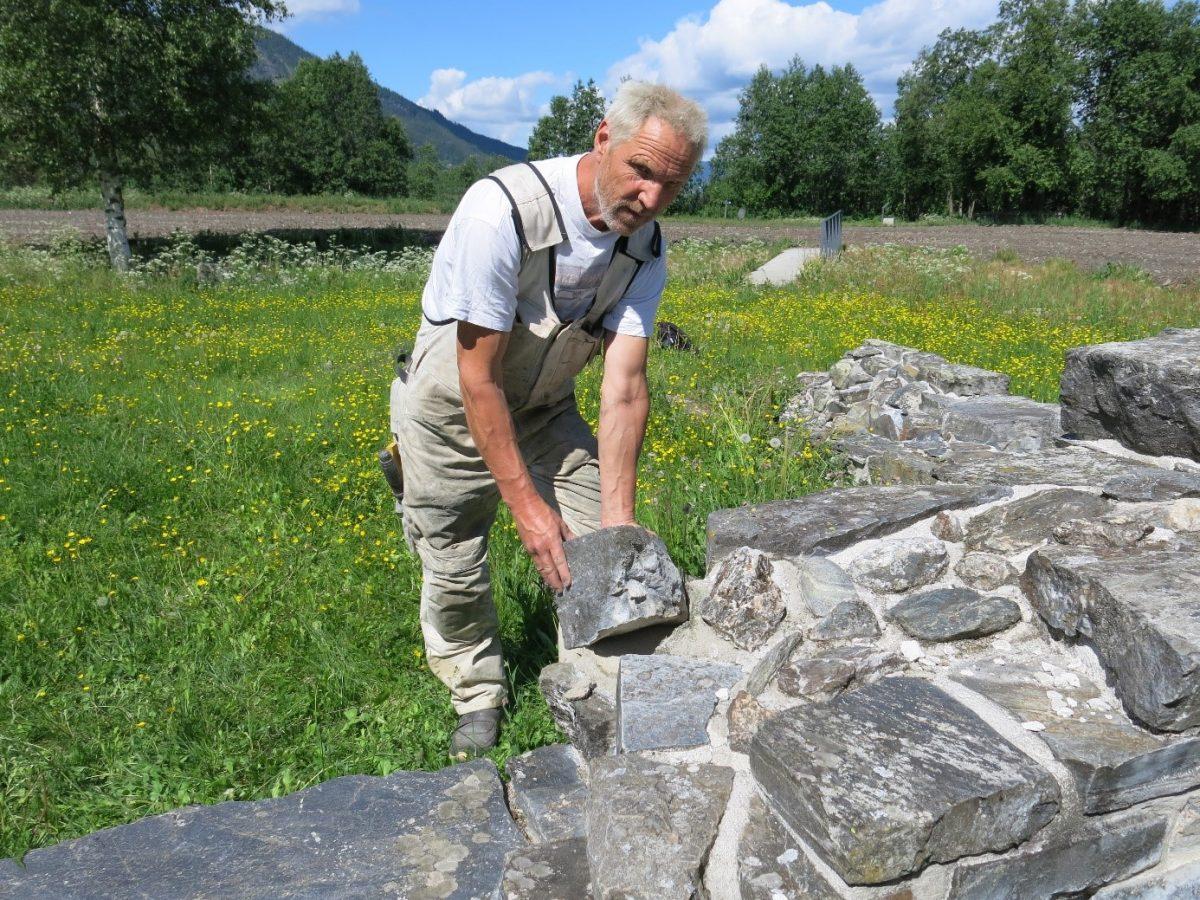 Håndverker reparerer lav steinmur