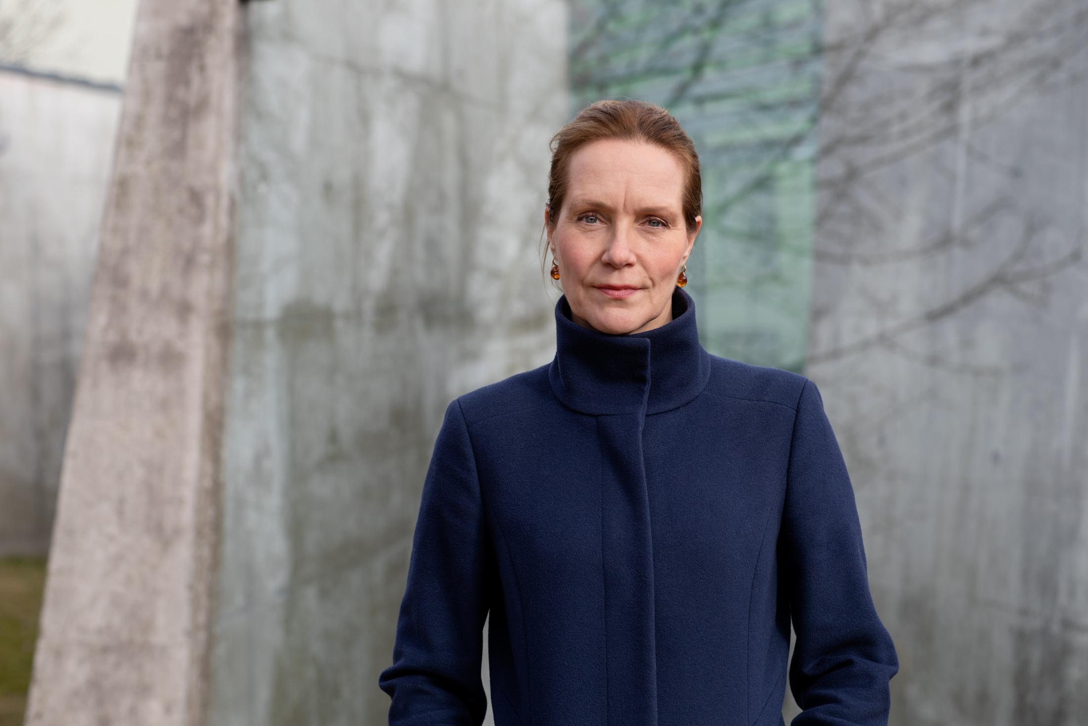 Bilde av riksantikvar Hanna Geiran foran en grå betongvegg