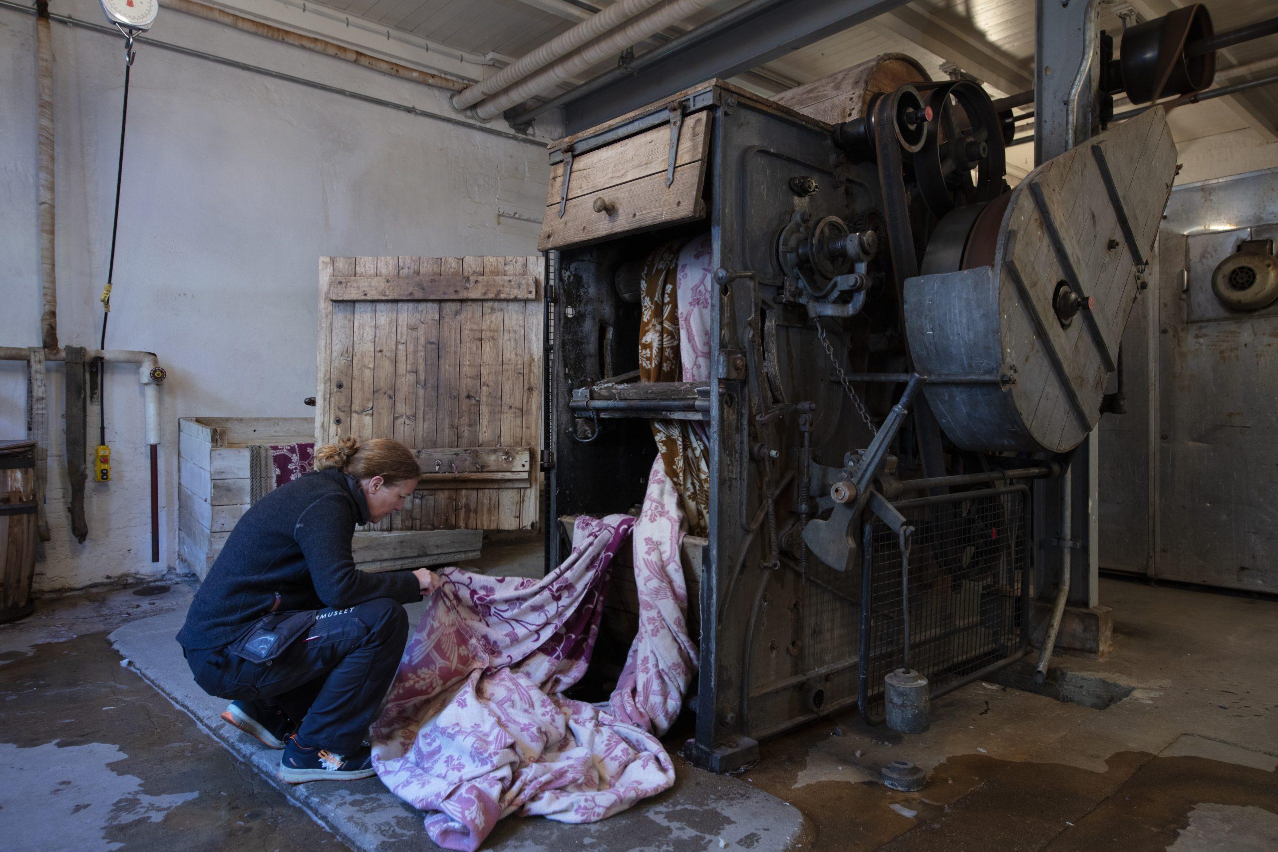 Bilde av kvinne som håndterer fargerike ullmateriale ved fargeriet fabrikken