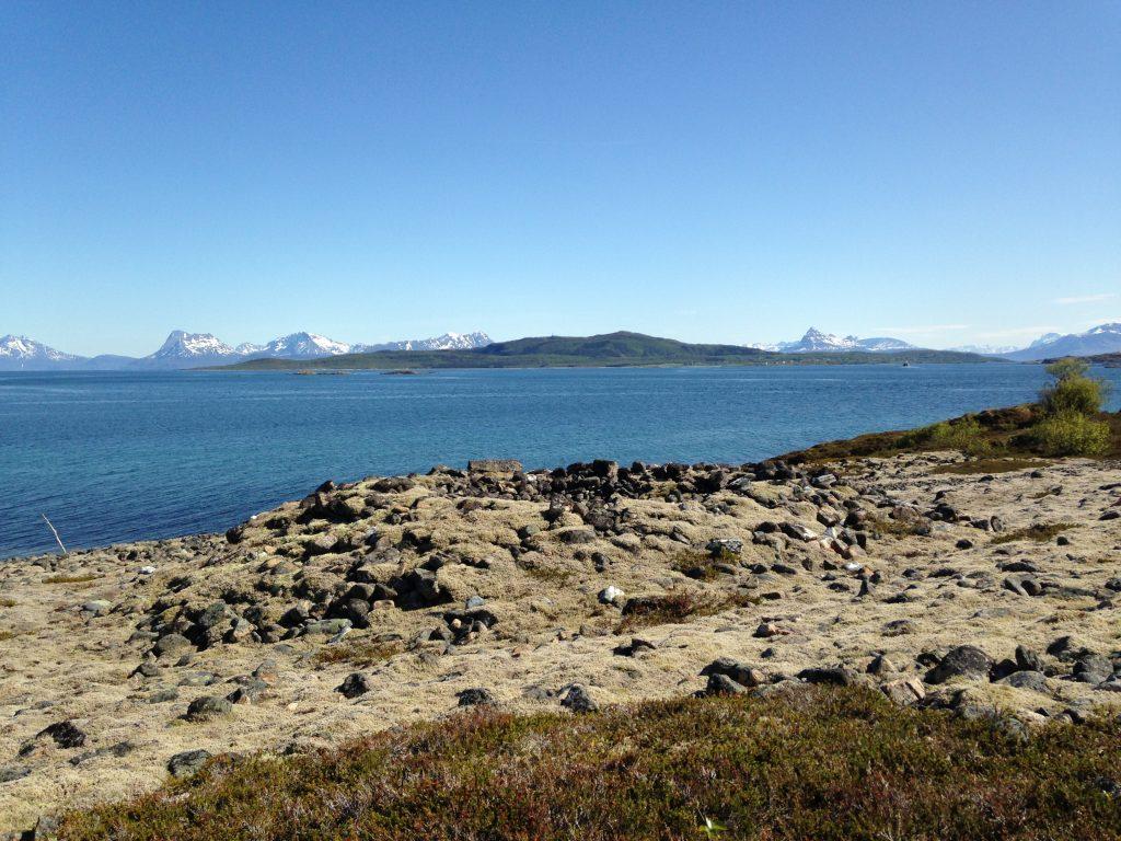 Foto av Bjarkøy. Øde landskap med flere graver. Nærbilde av gravrøys. Foto: Anne Karine Sandmo, Troms fylkeskommune