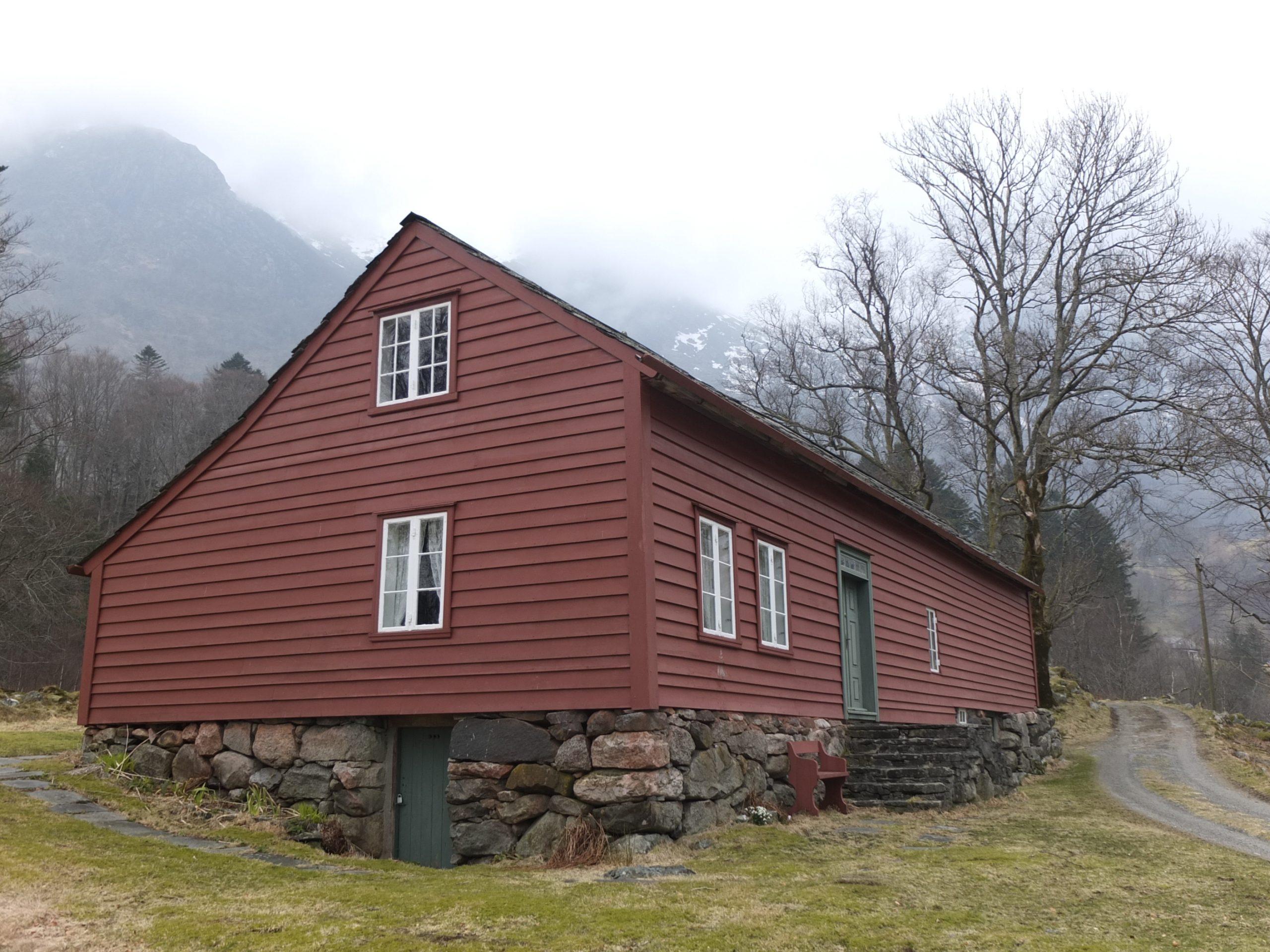 Bilde av Husmannsplassen Treo. Bygningen har rødmalt bordkledning og hvite smårutete vinduer. Bygningen står på gråstenmurte ringmurer og delvis kjellermur. Foto: May Britt Håbjørg, Riksantikvaren