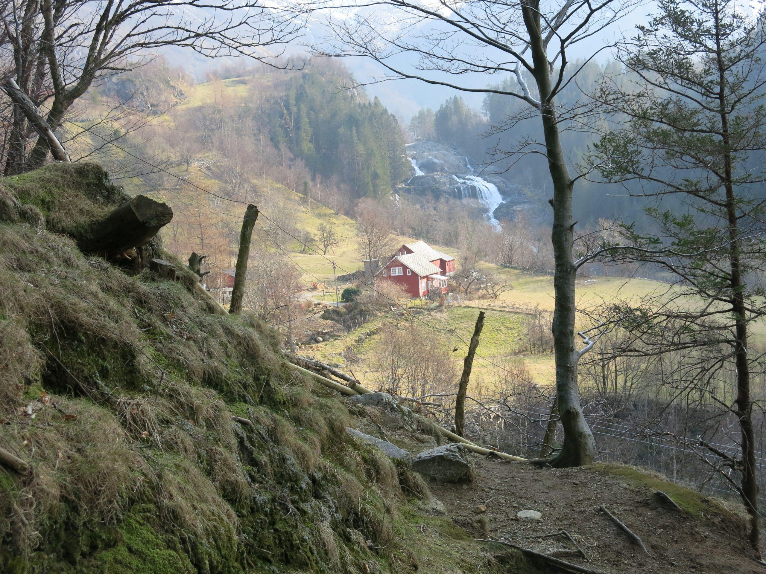 Overiktsbilde av Rosendals kulturlandskap med Hattebergfossen. Bildet er tatt oppe ved fjellet hvor man ser ned i dalen og bebyggelsen. Foto: May Britt Håbjørg, Riksantikvaren