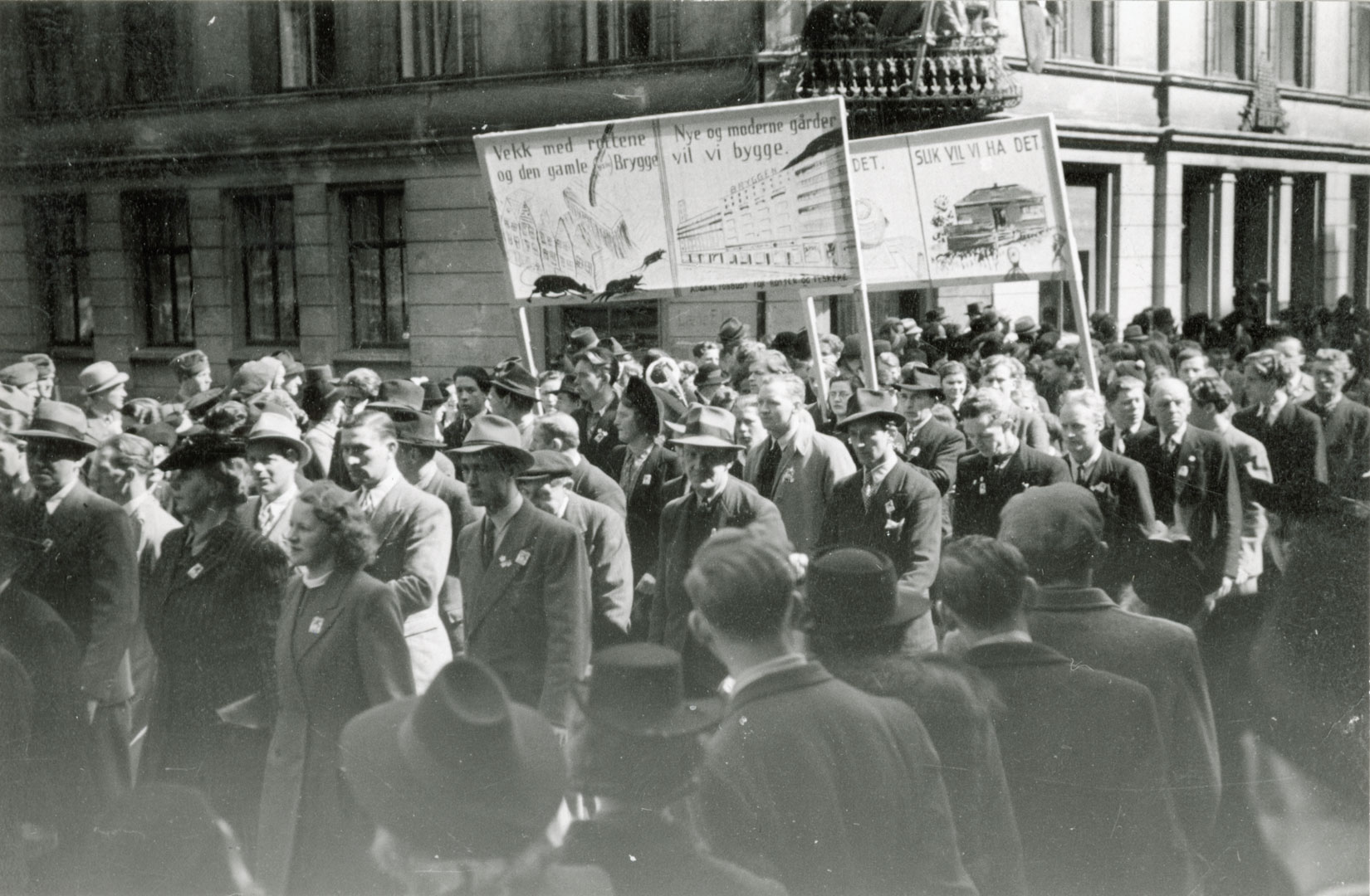"""Demonstration for the demolishing of Bryggen in Bergen in 1945/1946. There were calls to demolish """"German bryggen"""" around 1900, after the Second World War and in the 1950s. Today, Bryggen in Bergen is considered a national treasure and has been inscribed on the UNESCO World Heritage List. It is also one of Norway's top tourist attractions. Photo: Unknown, the Directorate for Cultural Heritage"""