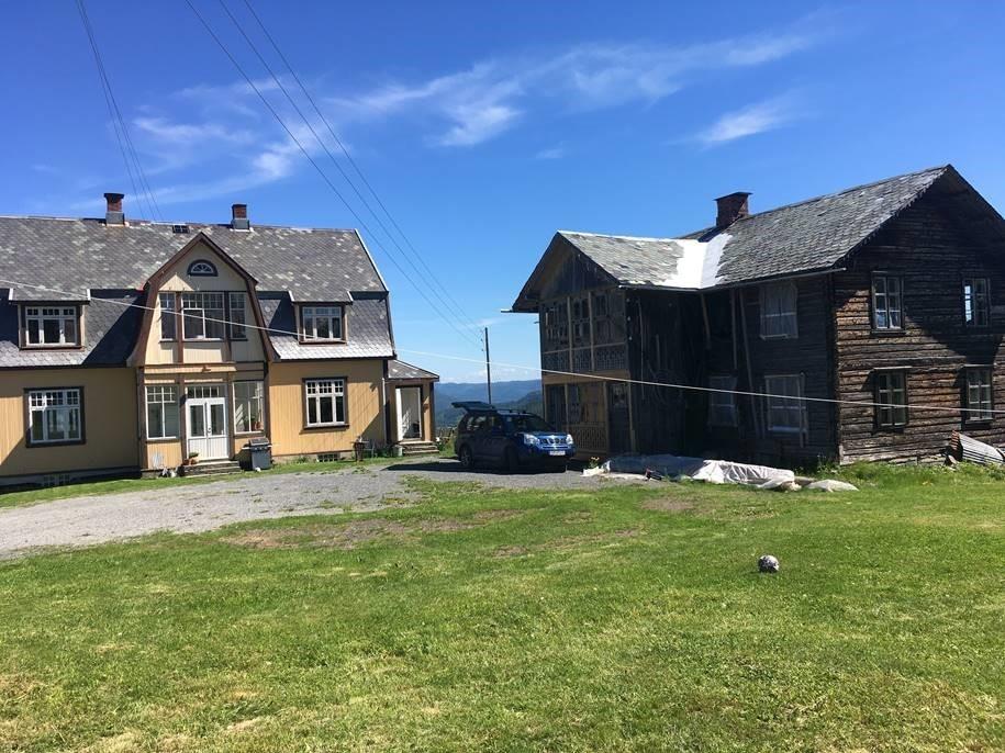 To hus på et tun med litt gressplen foran. Til høre et eldre tømmerhus og til venstre et gult hus i jugendstil.