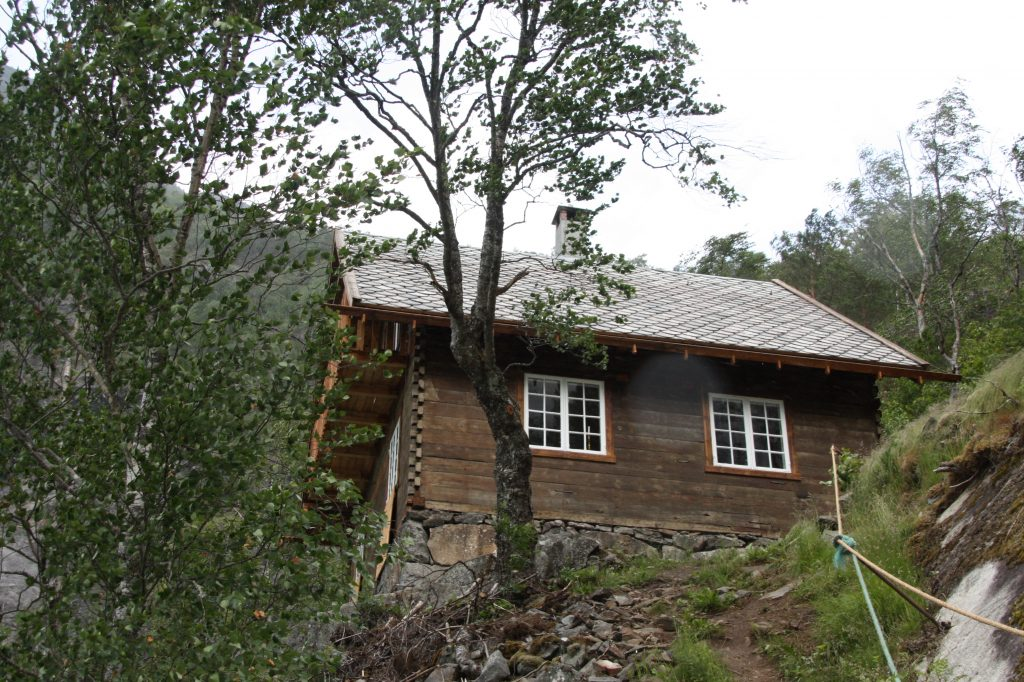 Wittgensteins hus sett nedanfrå i landskapet. Huset står på ei hylle i fjordlandskapet omslutta av fjell og trær.