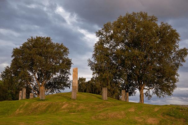 Bildet viser tinghaugen på Frosta med 13 bautasteiner i et vårlig landskap med grønne store trær i bakgrunnen