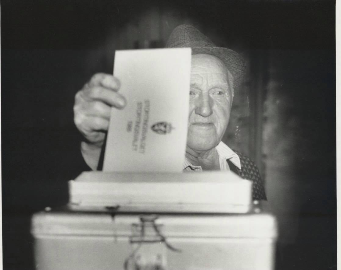 Eldre bilde av mann som putter stemmeseddel i valgurne.
